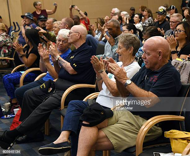 A group of veterans including Fred L Herr and his wife Peggy Herr react during a performance by recording artist John Fogerty and SixString Soldiers...