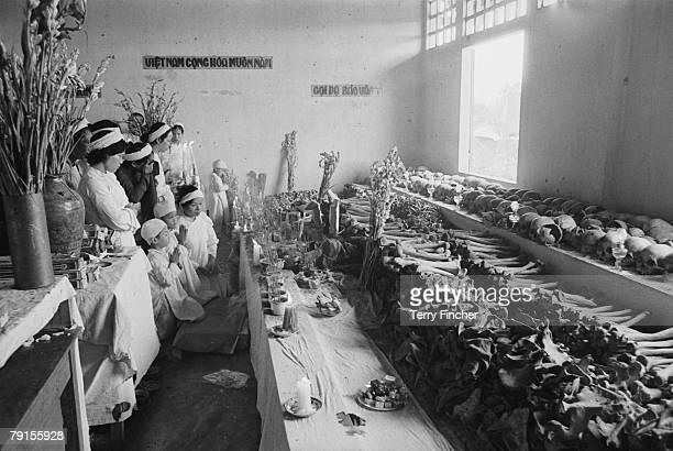 Group of Vietnamese Christians praying at a 'House of Death', Hue, Vietnam, circa 1970.