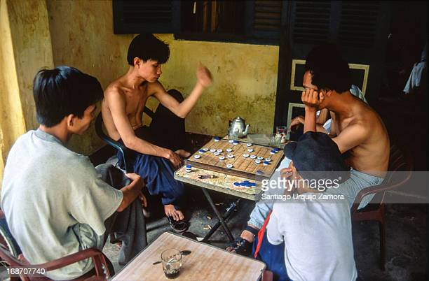 Group of Vietnamese men play relaxed XiangQi or Chinese Chess in the porch of their house in Hoi An. The laid-back lifestyle and the sincerity,...