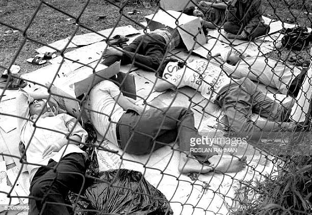 Group of Vietnamese refugees lie down 22 November, 1992 while on a hunger strike, which began 17 November to protest their inability to obtain...