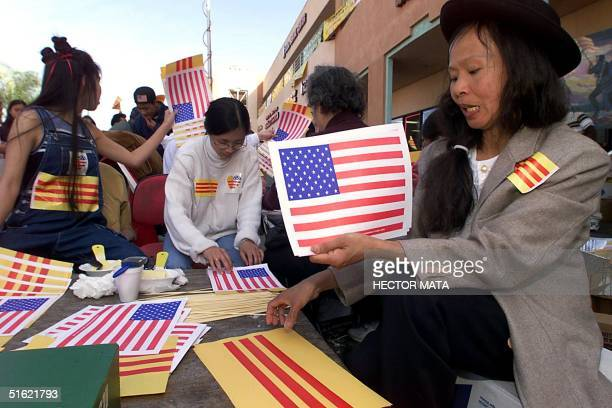 A group of VietnameseAmerican volunteers distribute US and Vietnamese flags to demonstrators near the entrance of a video shop 27 February in Little...