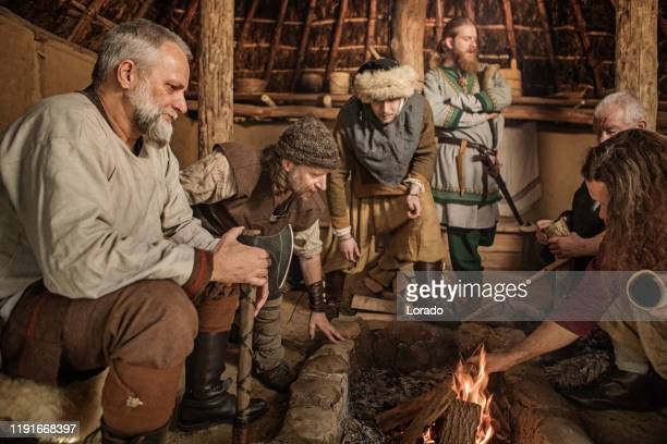 a group of viking male villagers in a hall - danish culture stock pictures, royalty-free photos & images