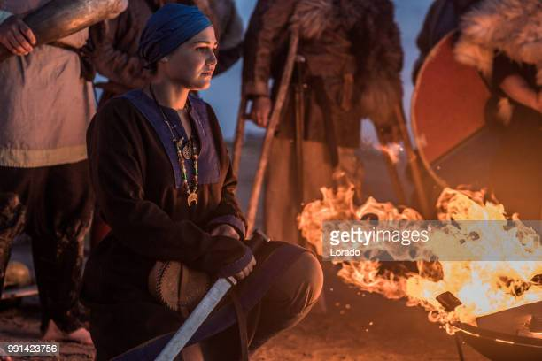 a group of viking warriors sitting around a campfire at night by the sea - historical reenactment imagens e fotografias de stock