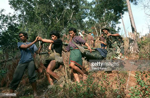 A group of villagers and Free Burma Rangers members carry Cha Ka Luu Moo a 17year old Karen boy through the mountain A couple of hours before the...