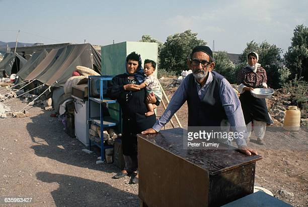 A group of villagers wait with their belongings near tents after an earthquake destroyed the Iranian village of Majil | Location Majil Iran