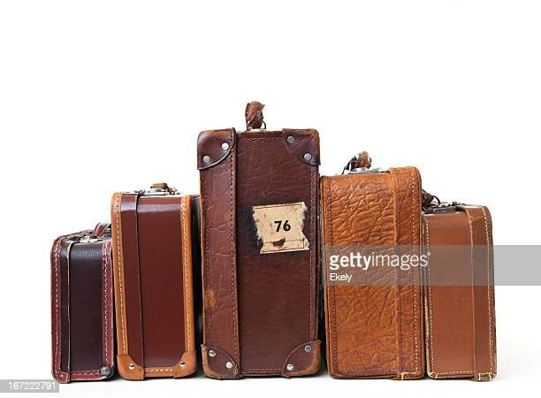 Group of vintage leather suitcases  with labels.