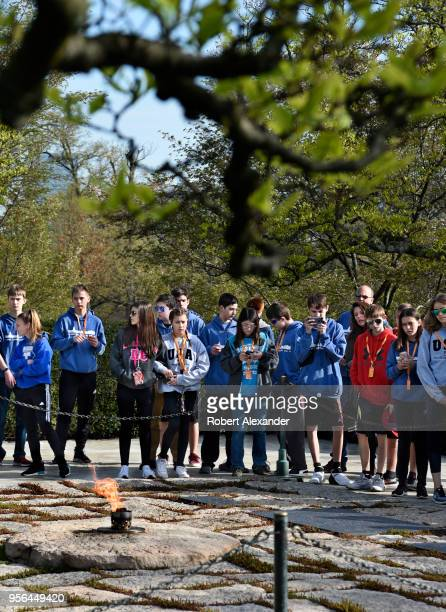 A group of visiting high school students stand at the gravesite of former US President John F Kennedy and his wife Jacqueline Kennedy Onassis and the...