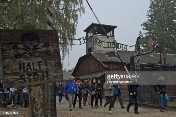 A group of visitors at the entrance to the Auschwitz I German Nazi concentration and extermination camp with the motto 'Arbeit macht frei' over the...