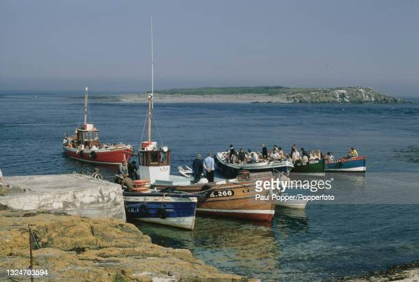 Group of visitors from the coastal village of Seahouses arrive in fishing boats at a jetty on one of the inner group of the Farne Islands off the...