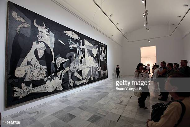 Group of visitors in front of Pablo Picasso's Guernica in Reina Sofia National Art Museum (Museo Nacional de Arte Reina Sofia).
