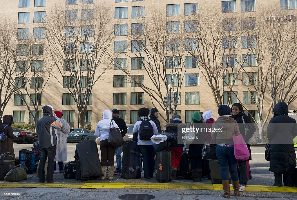 A group of visitors in town for the Inauguration of Barack Obama wait for their transportation home outside of their hotel on New Jersey Ave., on Wednesday morning, Jan. 21, 2009.