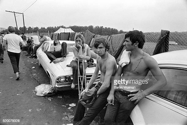 Group of visitors lean on the cars to rest at the Woodstock Music & Art Fair celebrated in Bethel, NY, August 15, 1969.