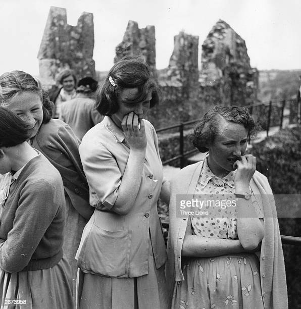 A group of visitors nervously wait their turn to kiss the Blarney Stone at Cork Ireland