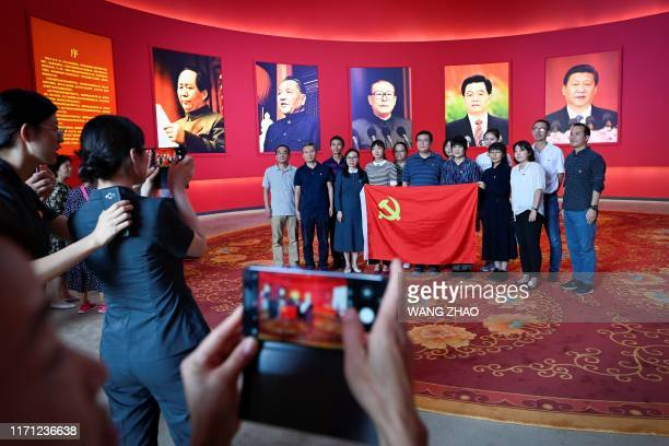 Group of visitors pose for a group photo with a Chinese Communist Party flag in front of pictures of late Chinese chairman Mao Zedong and former...