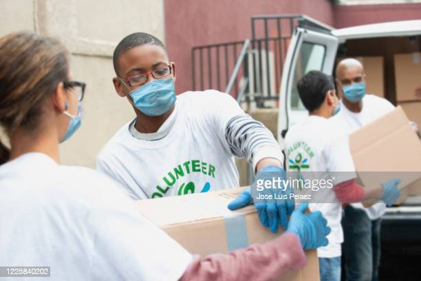 group of volunteer people delivering boxes - donation box stock pictures, royalty-free photos & images