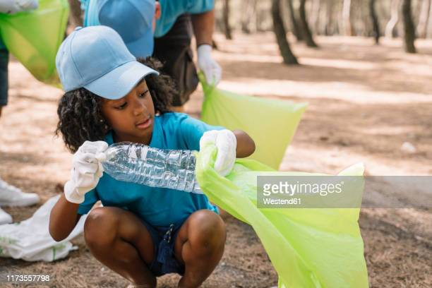 group of volunteering children collecting garbage in a park - kids with cleaning rubber gloves stock pictures, royalty-free photos & images