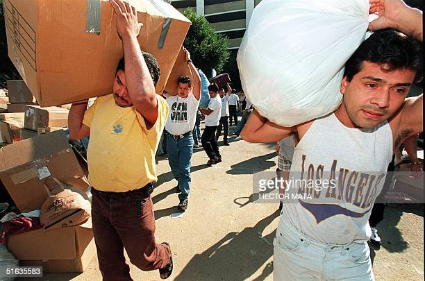 A group of volunteers carry boxes with food and medicines for the victims of Hurricane Mitch in Honduras 04 November Local officials fear more than...