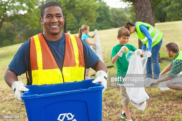 Group of volunteers cleaning up recyclables and trash at park