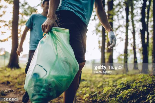 group of volunteers collecting garbage in park - sollevare foto e immagini stock