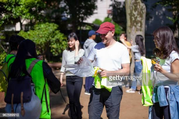 公園の清掃の準備をするボランティアのグループ - ボランティア ストックフォトと画像