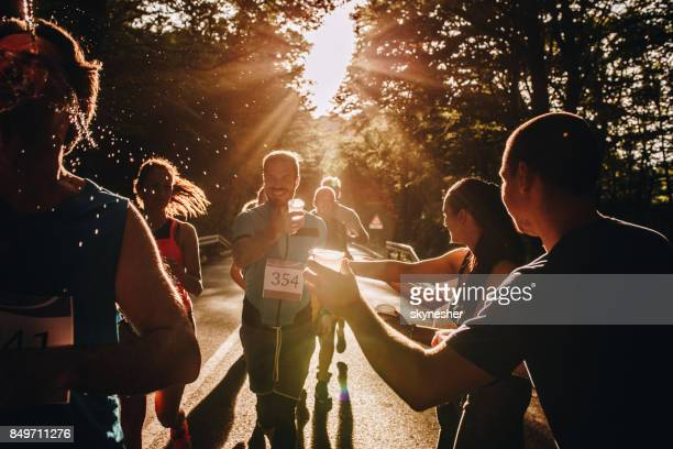Group of volunteers passing water to runners during marathon race at sunset.