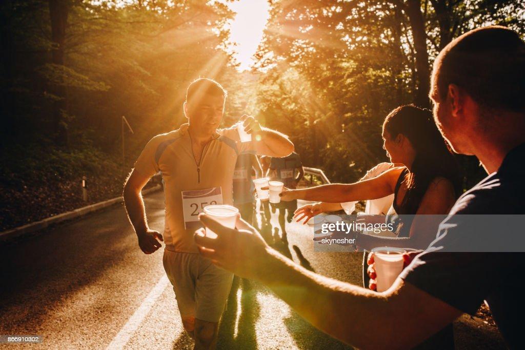 Gruppe von Freiwilligen Wasserlassen Läufer beim Marathonrennen bei Sonnenuntergang. : Stock-Foto