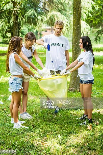 group of volunteers picking garbage - pjphoto69 stockfoto's en -beelden