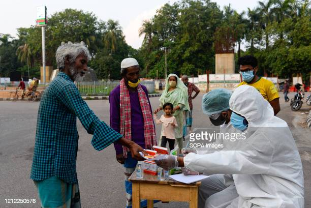 Group of Volunteers wearing protective suits give free medical treatment to homeless people amid coronavirus crisis. Volunteers from Dhaka University...