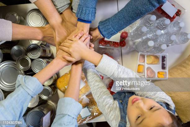 group of volunteers with hands together - food bank stock pictures, royalty-free photos & images