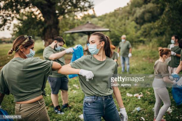 group of volunteers with surgical masks cleaning nature together - environmental issues stock pictures, royalty-free photos & images