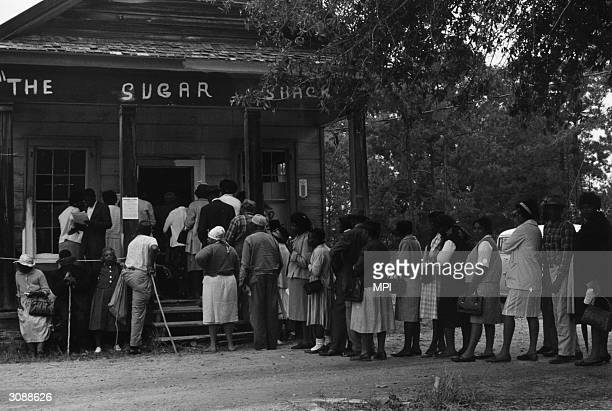 Group of voters lining up outside the polling station, a Sugar Shack small store, in Peachtree, Alabama, after the Voting Rights Act was passed the...