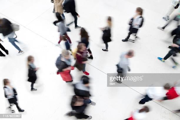grupo de personas que caminan, vista elevada, efecto desenfoque de movimiento - grupo organizado fotografías e imágenes de stock