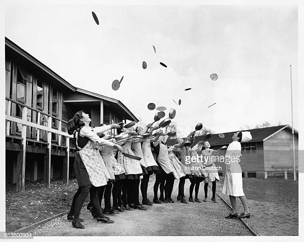 A group of wartime evacuees take time to celebrate Shrove Tuesday the day before Lent by tossing pancakes into the air