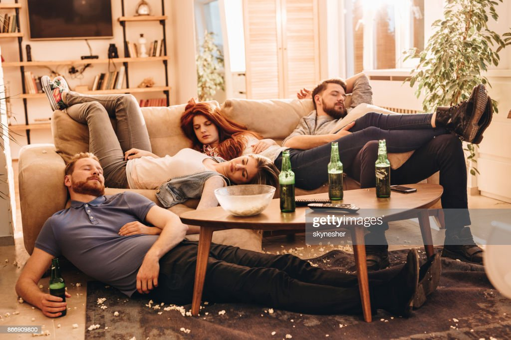 Group of wasted friends sleeping after party in the living room. : Stock Photo
