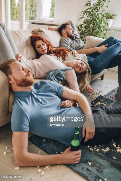group of wasted friends sleeping after the party in the living room. - hangover after party stock pictures, royalty-free photos & images