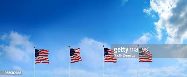 group of waving american flags hanged at tall poles in a row over blue sky - independence day holiday stock pictures, royalty-free photos & images
