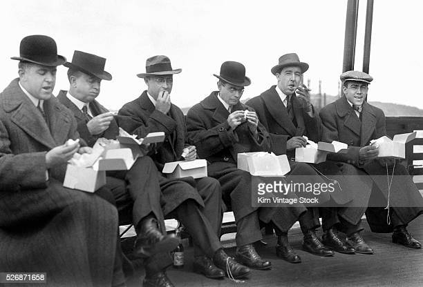 Group of well dressed business men enjoy a boxed lunch seated along the railing of a ferry boat in the early 20th century.