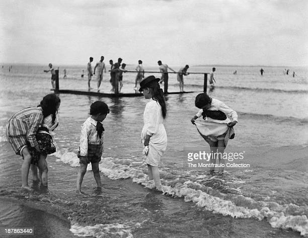 Group of well dressed children paddling on a Boston beach with men and boys on a floating pontoon in background Boston USA circa 1895