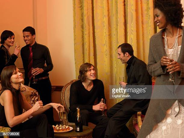Group of Well-Dressed Young Men and Women Drink Champagne at a Dinner Party