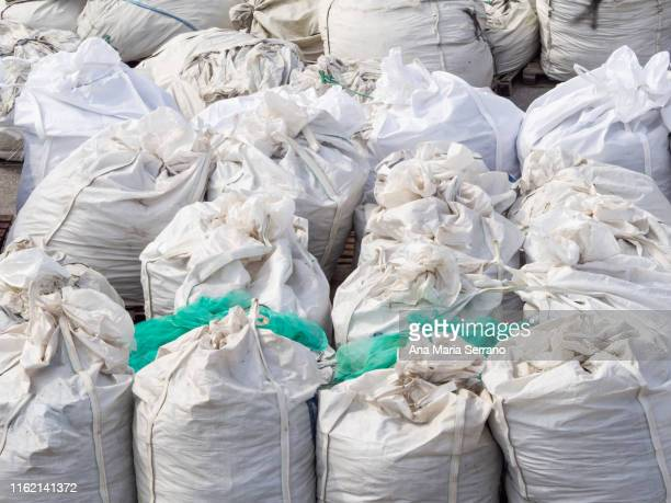 a group of white plastic bags filled, closed and ordered - rubble stock pictures, royalty-free photos & images