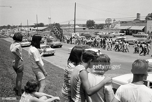 A group of white youths watch and wave confederate flags as a group of Freedom Marchers walks through Senatobia Mississippi on the fifth day of the...