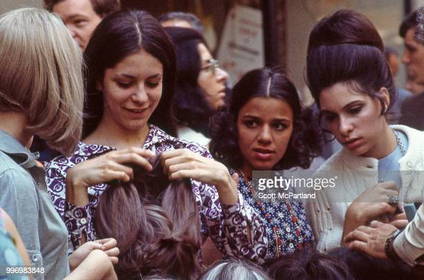 A group of woman examine wigs from sidewalk vendor's display on an unidentified crowded Manhattan street New York New York May 1 1970