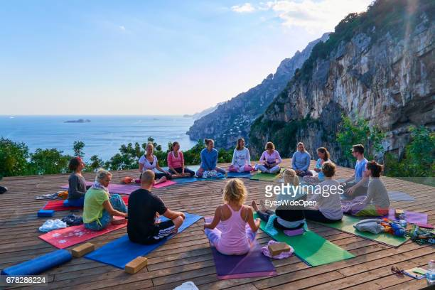 A group of Woman is practicing Yoga Meditation and Pranayama at the Yoga Retreat La Selva overlooking Positano and the Ocean of the Amalfi Coast on...