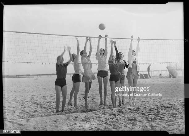 Group of women all reaching above a net for a volleyball.