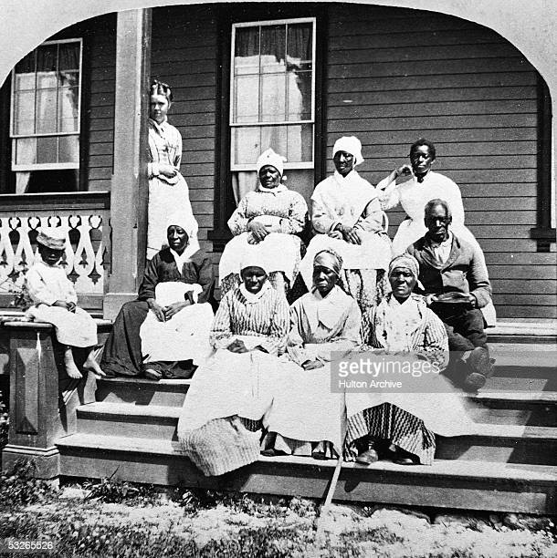 Group of women and a man, presumably slaves, sit on the steps of the Florida Club, St. Augustine, Florida, mid 19th Century. A white woman, possibly...