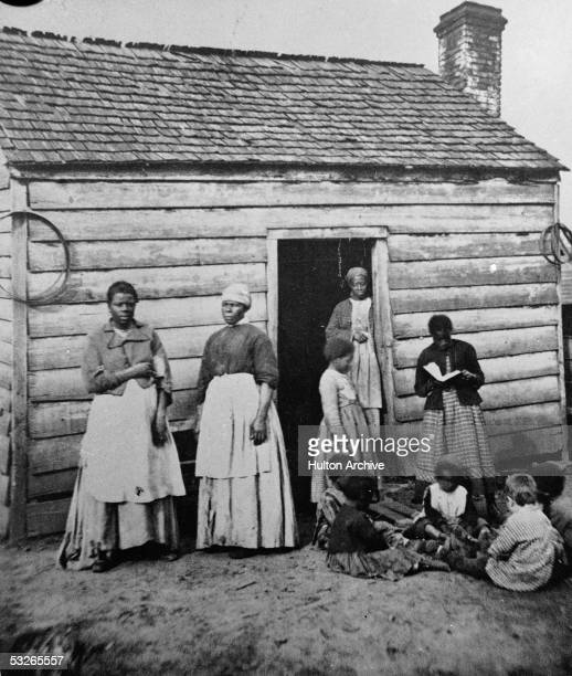 Group of women and children, presumably enslaved, sit and stand around the doorway of a rough wooden cabin, Southern United States, mid 19th Century....