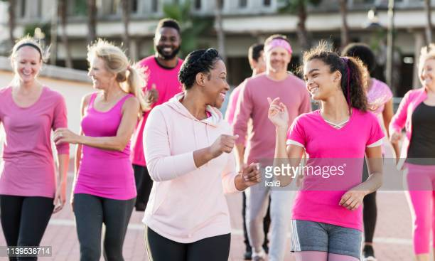 group of women and men in pink, at breast cancer rally - marching stock pictures, royalty-free photos & images