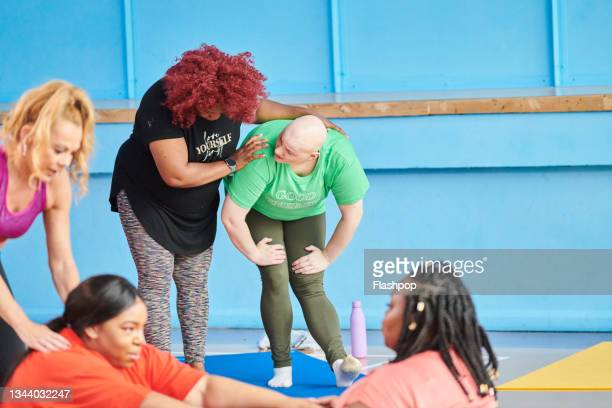 group of women at a yoga class - human limb stock pictures, royalty-free photos & images