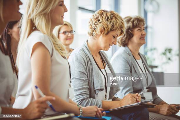 group of women attending a seminar - attending stock pictures, royalty-free photos & images
