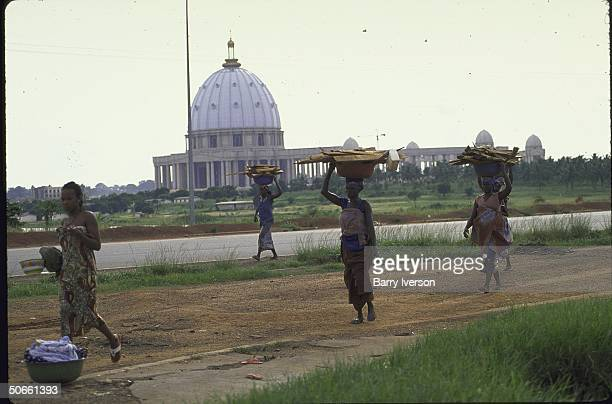 Group of women balancing baskets walking on road with St Peter'slike Basilica of Our Lady of Peace looming in rear Basilica is pet project of...